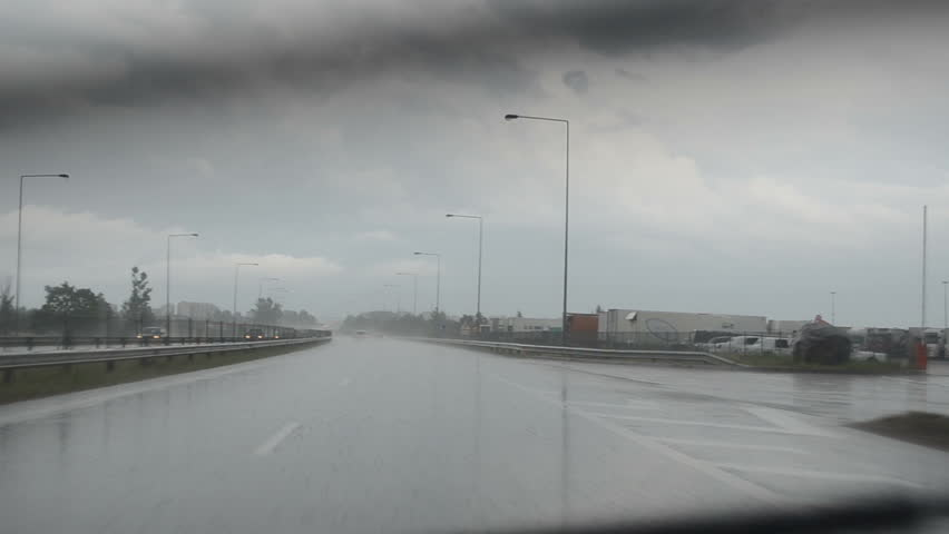Rain water river on highway road and cars driving in danger weather conditions. - HD stock footage clip