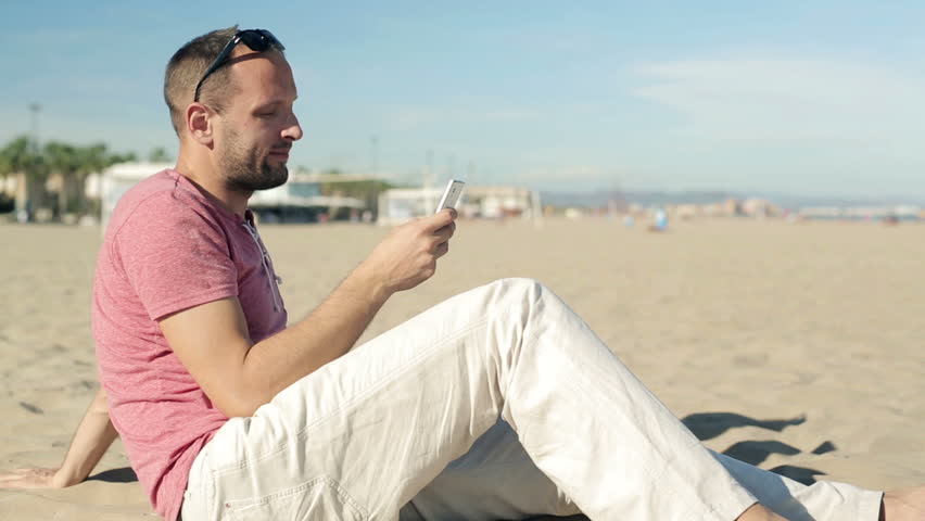 Young man texting on smartphone on the beach