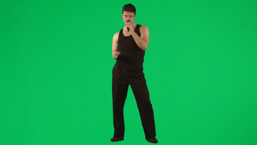 Man singing with a microphone against green screen - HD stock video clip