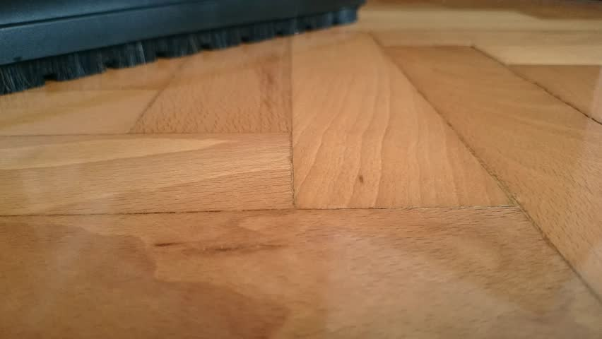 Cleaning a parquet floor with vacuum cleaner close up high for Hardwood floors meaning