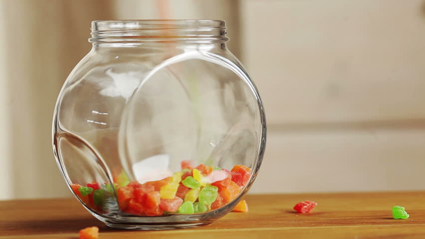 Jelly cubes and berry jelly candy passing by in a jar