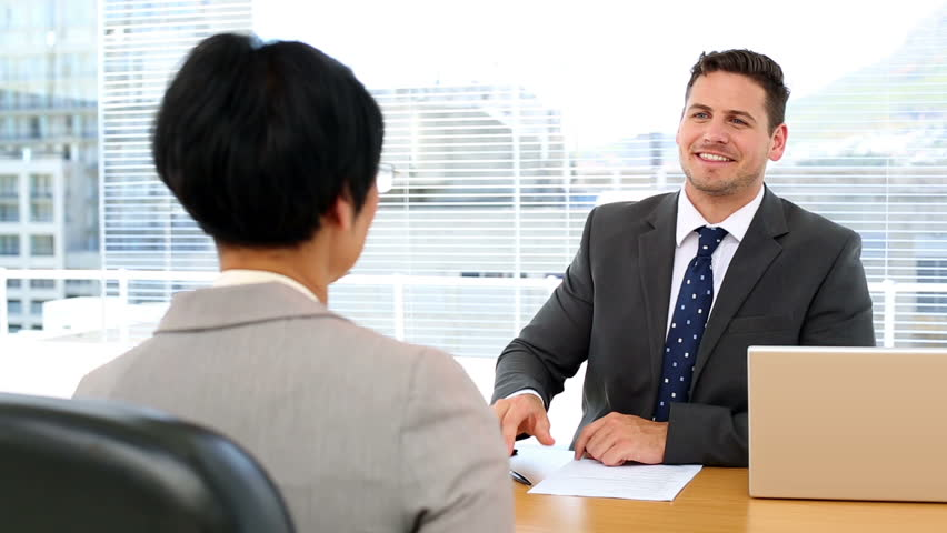 Handsome businessman shaking hands with interviewee in the office - HD stock footage clip