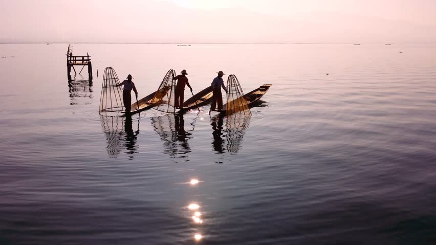 Myanmar, Burma Inle Lake fishermen fishing on traditional boat at sunset. Beautiful reflection of evening sun and silhouettes in water. Famous tourist travel destination 4k ultra high definition video - 4K stock video clip