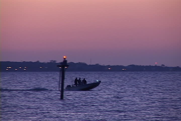 Fishermen speed a small fishing boat across the waters of for Fishing in mobile al