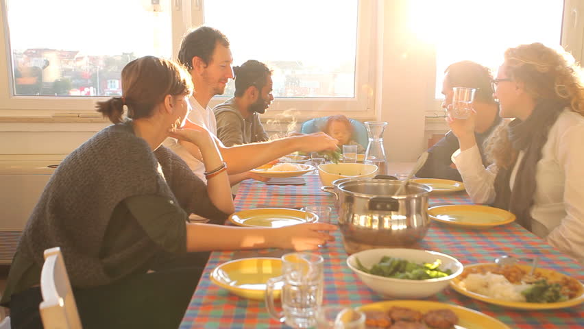 Group of friends eating lunch at home with flare