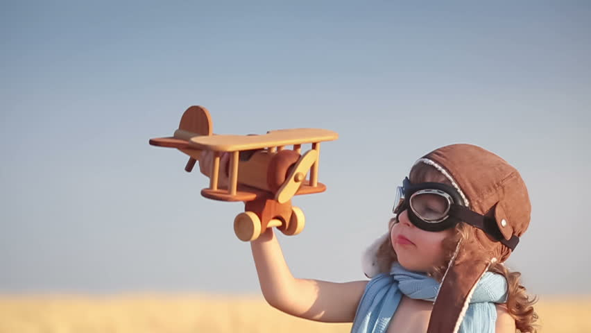 Happy kid playing with toy vintage airplane against summer blue sky background. Travel concept. Slow motion