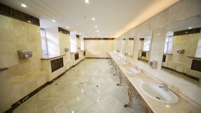 Spacious public toilet with marble flooring and countertops for stylish sinks