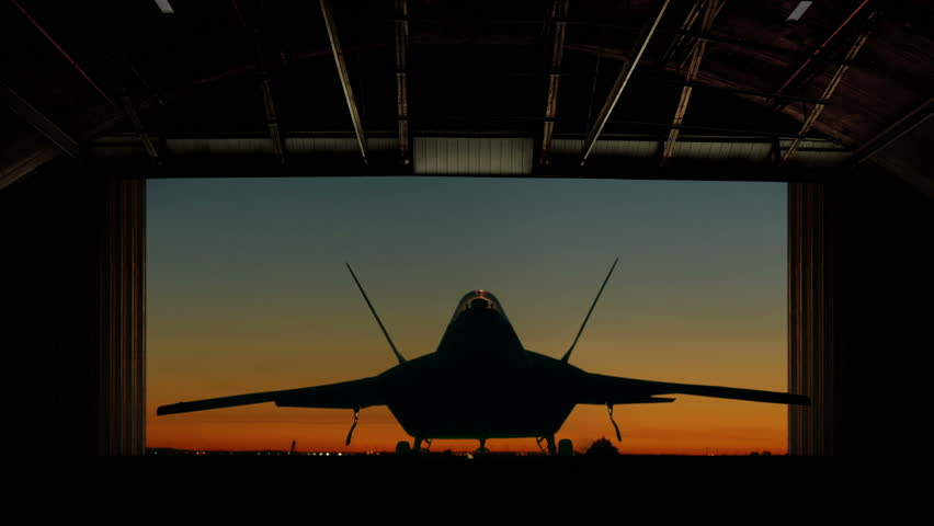 An F-22 Raptor Stealth Fighter is revealed as hangar doors open slowly.