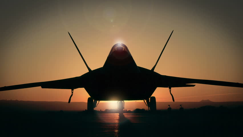Slow jib shot of a silhouetted F-22 Raptor, a stealth combat aircraft.