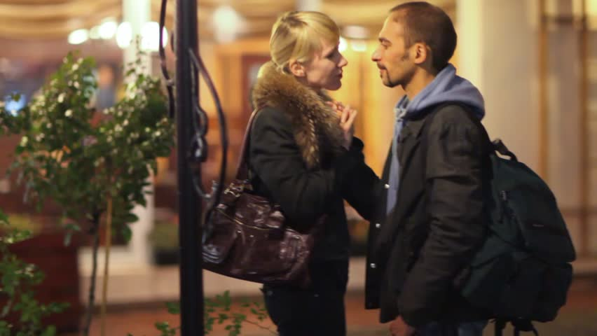 man and woman talking and embracing on night street, vertical panning  - HD stock footage clip