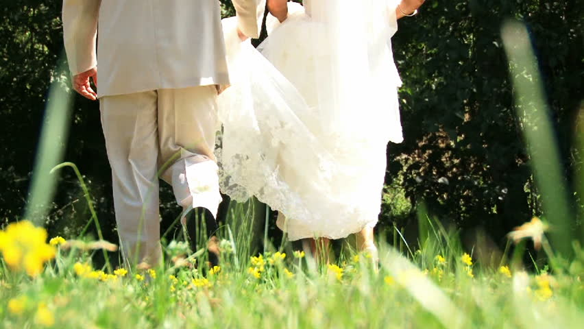 Bride and Groom walking together in flower field. - HD stock video clip