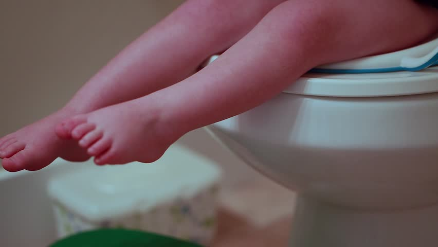 A toddler boy being potty trained on the toilet