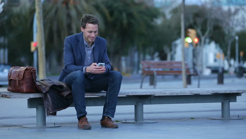 Smart phone man talking and texting in city night using smartphone. Handsome young business man smiling happy wearing suit jacket. Urban male professional in his 20s in Barcelona, Spain. - HD stock footage clip
