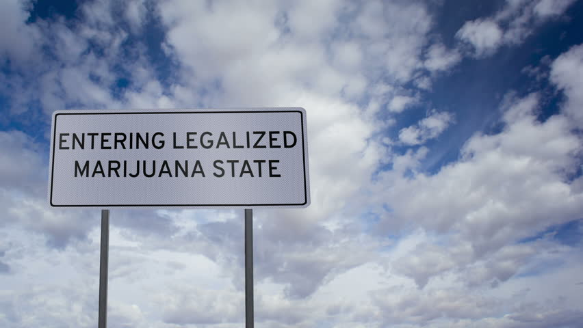 Highway road sign with the words ENTERING LEGALIZED MARIJUANA STATE with a fluffy, white clouds time-lapse background.