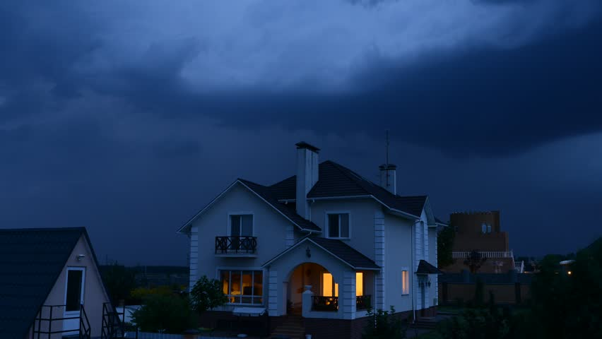 time lapse of night house against a dramatic sky with a lightning - HD stock footage clip