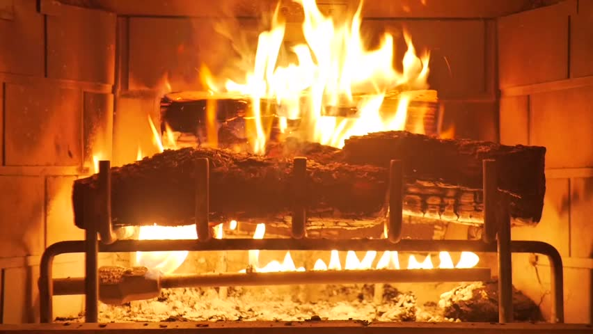 Medium shot of a yule log burning in a fireplace.