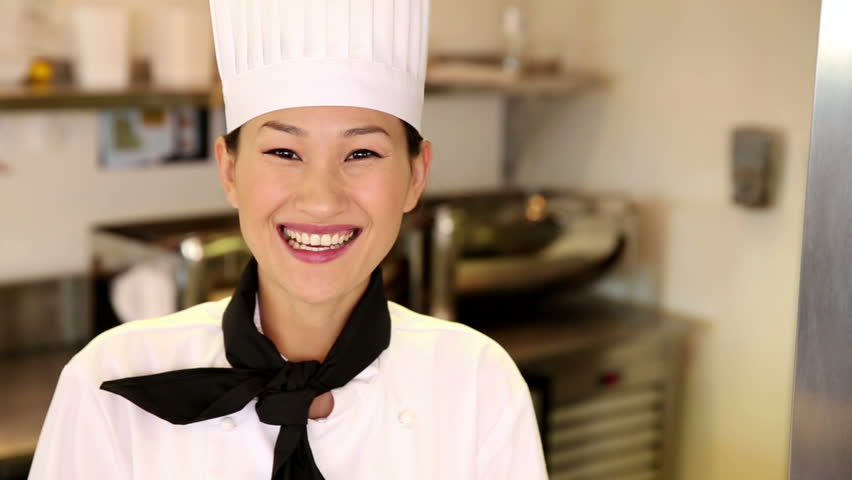 Happy chef smiling at camera giving thumbs up in commercial kitchen - HD stock video clip