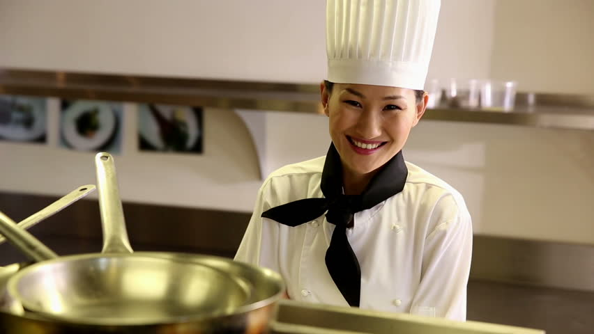 Happy chef smiling at camera from behind a shelf in commercial kitchen - HD stock footage clip