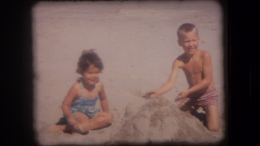 UNITED STATES - CIRCA 1950s: Old home movie film: Boy and girl at sandy beach