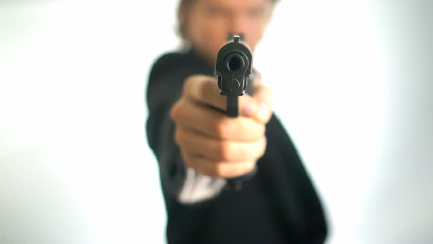 Man in suit aims his gun. A threatening stance, aiming down the sights of his pistol, police, mafia criminal or mercenary. Focus is on the barrel with a one hand pistol grip.