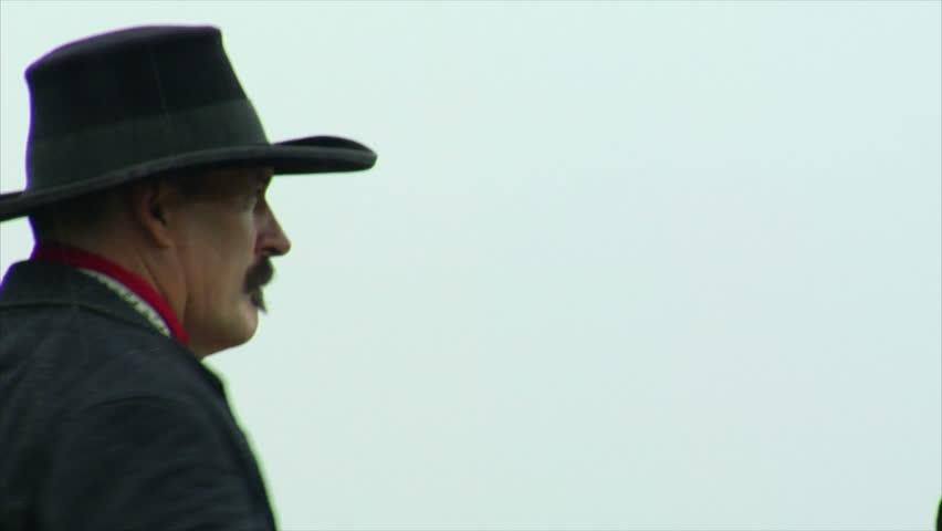 VIRGINIA - 2013.  Western era, Old West Cowboy, Marshall, Sheriff, Outlaw on horseback.  Circa 1860-1890s.  Firing Colt revolver pistol with black powder smoke.  Cowboy Shoot-out, gunplay
