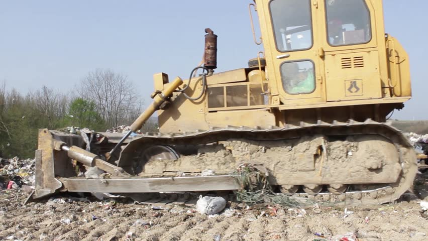 7/35 SRBIJA,KRUSEVAC,2014. Bulldozer (tractor) pushes a pile of trash at landfill. Vehicle flattening garbage to waste. Bulldozer moves non biodegradable garbage at the dump. Dogs searching food.30fps - HD stock footage clip