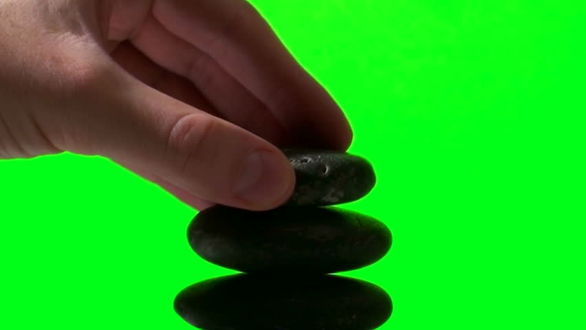 Hand stacks Zen rocks against green screen - HD stock footage clip