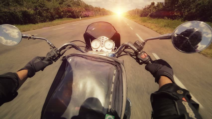 A motorcycle road adventure going forward to the sun in high speed. pov at sunset.