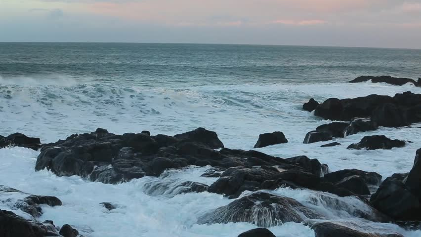 Ocean waves crashing on the rocks in the western part of Iceland in the sunset light