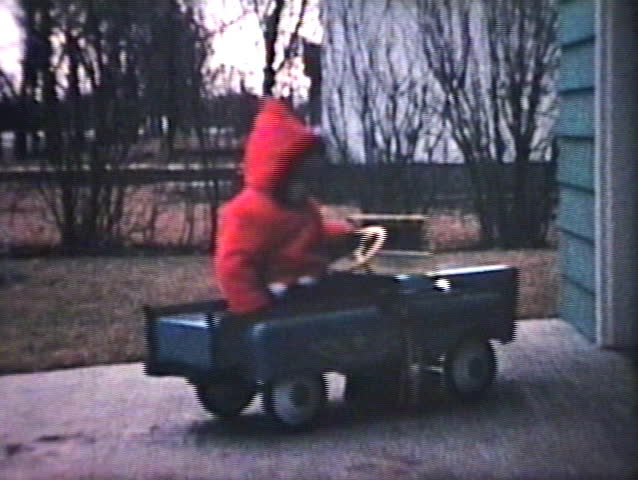 A little boy rides his funky new pedal car outside and bumps into his dad's real car in the driveway. (Vintage 8mm film)