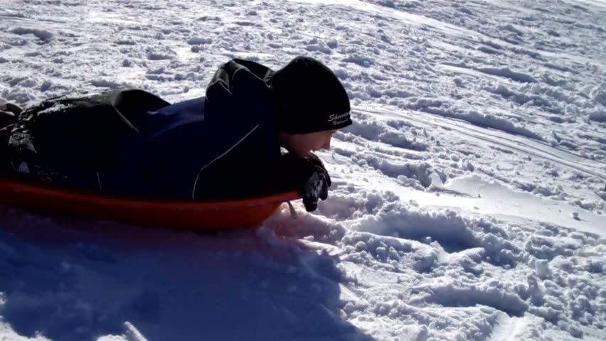 boy tobogganing head first down a snowy hill - HD stock footage clip