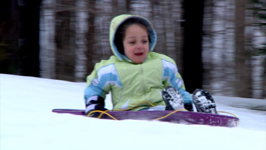 A little girl goes sled ridding.  Slow motion. - HD stock footage clip