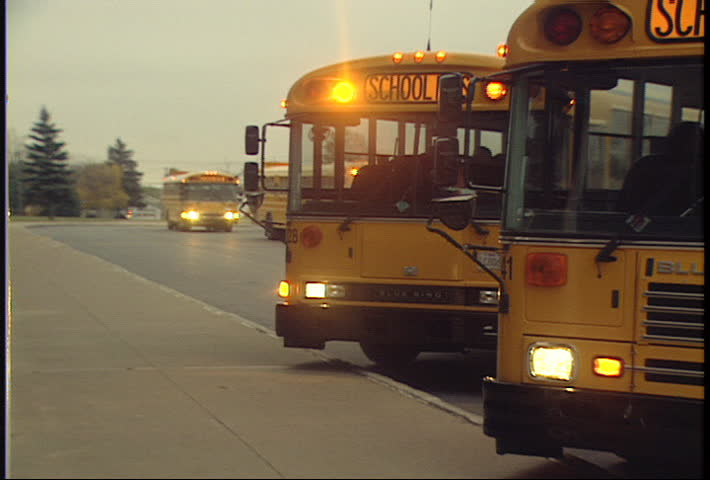 rack focus of school buses lining up to drop off kids - SD stock video clip
