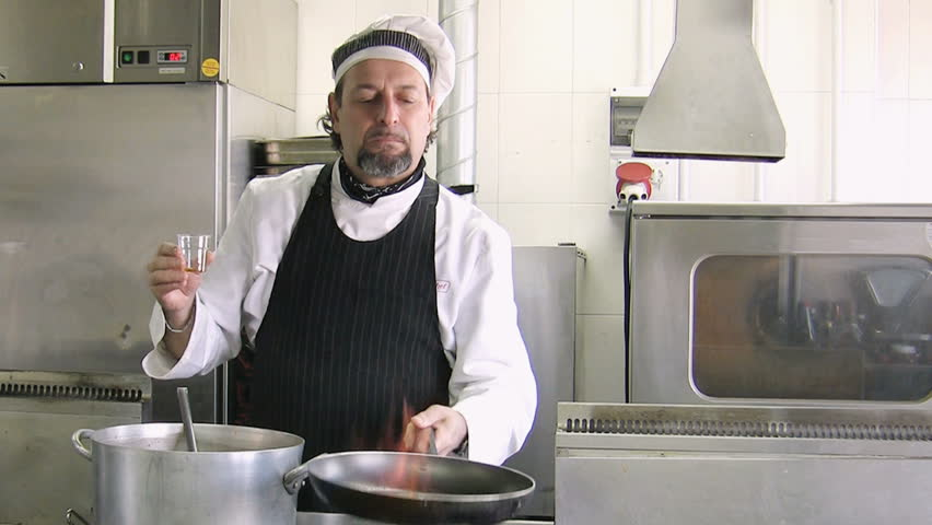 Mature chef holding pan and doing a flambe. Front view - HD stock footage clip