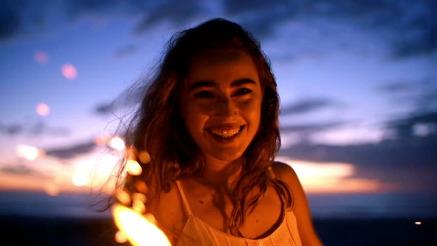 Smiling young woman with sparkler at sunset in slow motion - HD stock footage clip