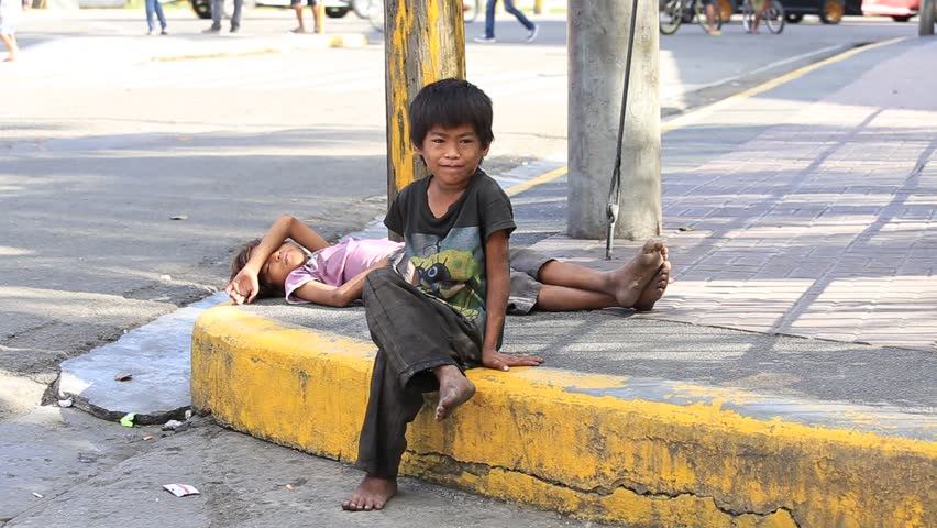 CEBU, PHILIPPINES - MARCH 15, 2014 : Poverty in Philippines, a unidentified beggar boys live on the street. Nearly one of every three Filipino children aged 4 to 10 is underweight.