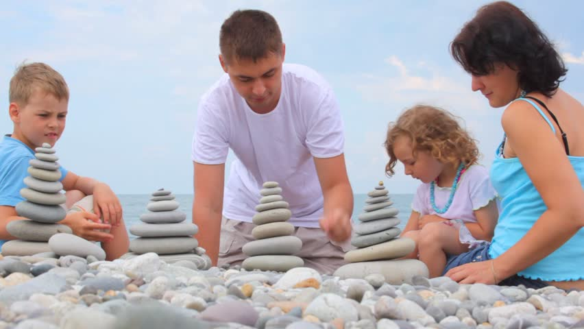 family of four building stone stacks on pebble beach, sky in background