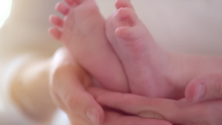 Baby feet in mother hands. Newborn Baby's feet on female Heart Shaped hands closeup. Mom and her Child. Happy Family concept. Beautiful conceptual video of Maternity. 1080p Slow motion. Slowmo 240fps
