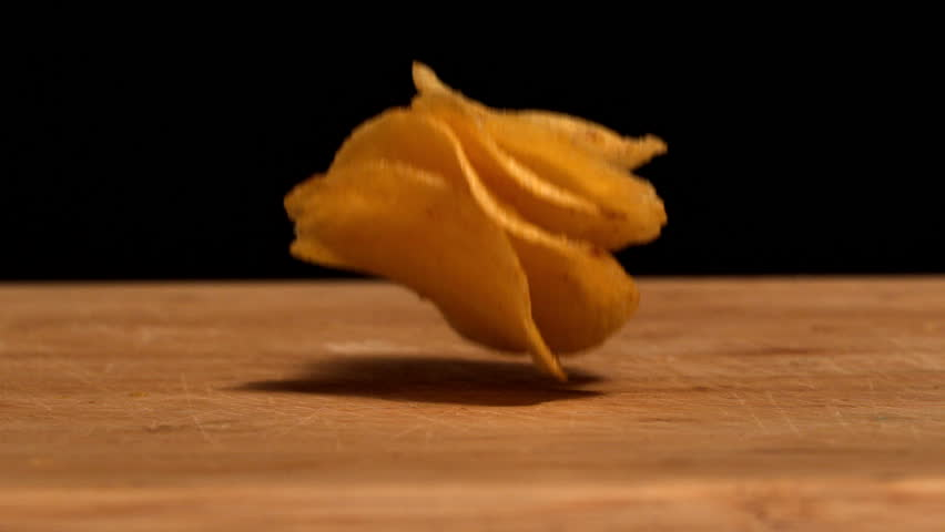 Chips falling on wooden table in slow motion