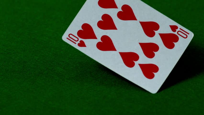 Ten of hearts falling on casino table in slow motion