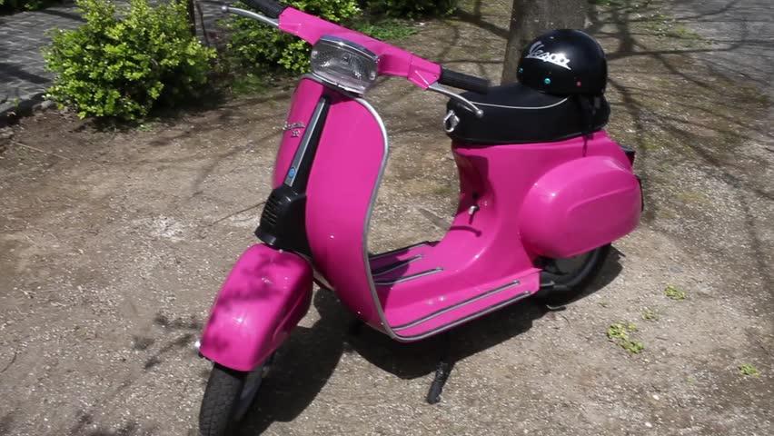 ANGUILLARA SABAZIA, LAZIO, ITALY - APRIL 6, 2014: Nice pink vintage 50s Vespa Scooter, iconic symbol of Italy, manufactured by Piaggio.
