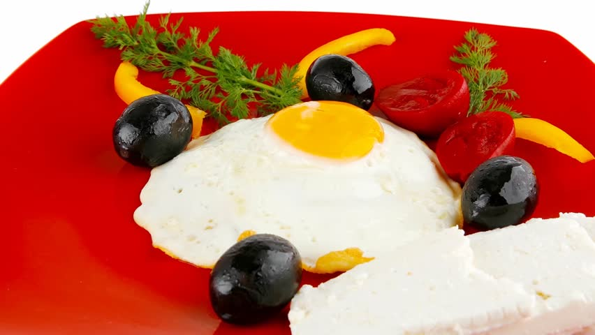 fried scrambled eggs eye with white goat feta cheese on red plate with black olives and vegetables 1920x1080 intro motion slow hidef hd