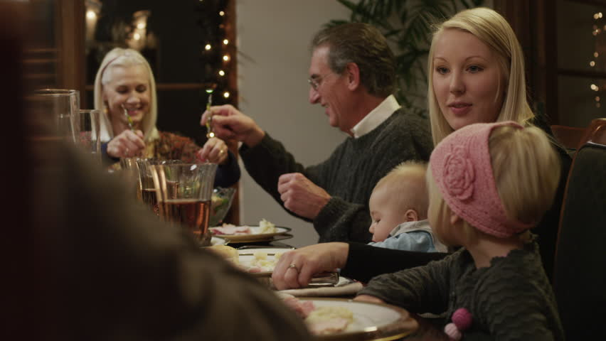 Medium Shot Pan Family with children (2-5 months,2-9 years) having Christmas dinner