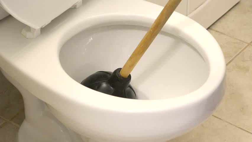 Unclogging a toilet. Person doing cleaning job. Maid in a hotel or motel. Taking care of the washroom or bathroom hygiene. Plumber working in a toilet. Manually unclogging the toilet.