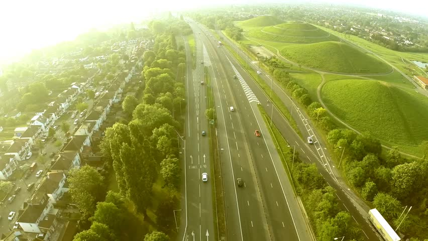Aerial view of a truck and other traffic driving along a road on the outskirts of a city in the UK