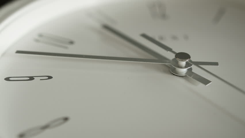 Close up white Clock face. A close up shot of a white clock face with shallow depth of field and a silver second hand ticking by. Full HD filmed on the Blackmagic Cinema Camera.