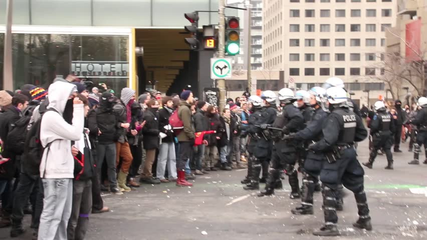 Montreal, QC, Canada - February 26th 2013 - Intense clashes and riot. A riot officer hits and catch a protester violently while another protester is being carried away by officers in the background.