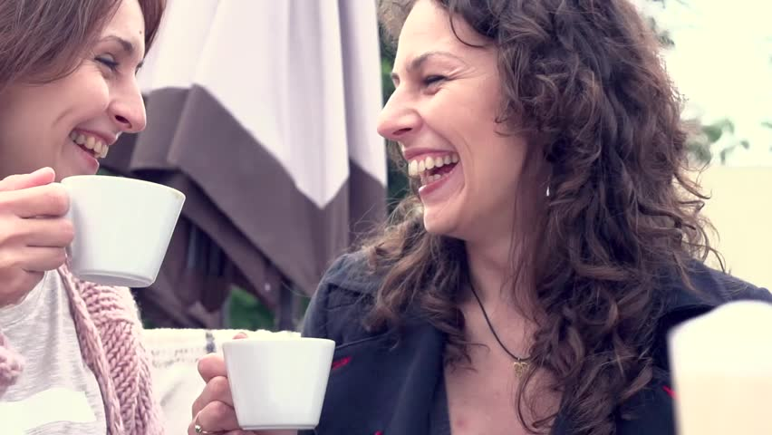 Beautiful women drinking coffee in cafe and talking. High speed camera shot 1080p. Slow motion video footage