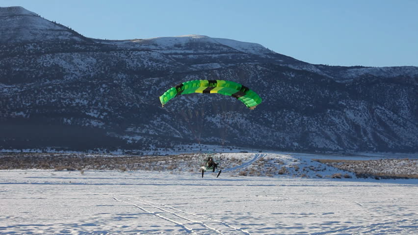 Powered parachute landing past friends on ice and snow covered lake in winter. Central Utah winter recreation and sport. Pilot in aircraft and friends watching. - HD stock video clip