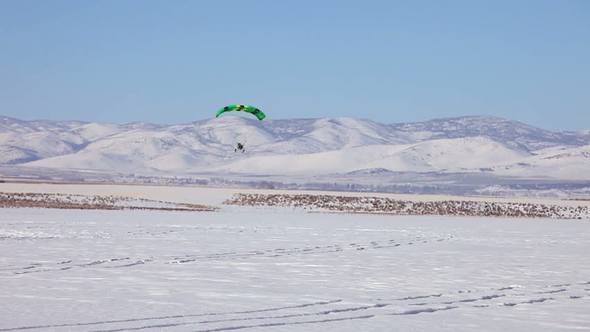 Powered parachute flying over ice and snow covered lake in winter. Central Utah winter recreation and sport. Pilot in aircraft. - HD stock footage clip